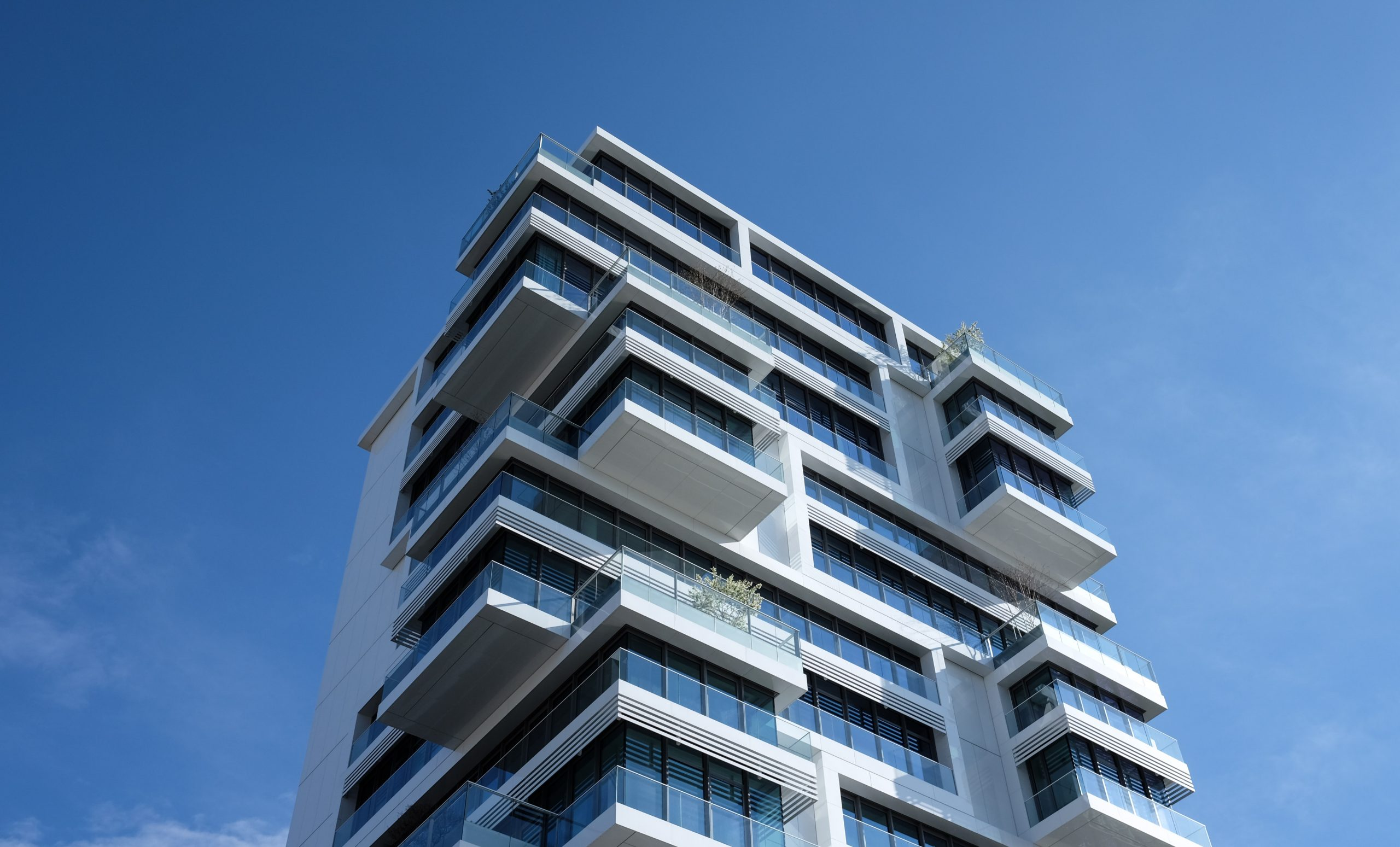 A low angle show of condo building centered in front of a bright blue sky.